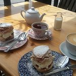 Jam and cream scones with tea and coffee.