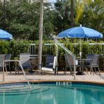 Sparkling outdoor heated pool with seating area and pool towels.