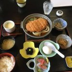 Pork cutlet, sliced raw fish, soup, rice, and vegetables.