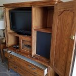 TV dresser cabinet very old, used, and not easy to use. Room needs new furniture.