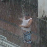 Shot from my room of a man showering under a rain gutter during a storm
