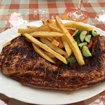 A huge pork chop with hand cut chips