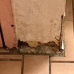 Floor/wall in women's bathroom is rotting away. Torn booth seat, dirty floor, worn wood on table
