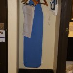 Iron and ironing board right next to the bathroom