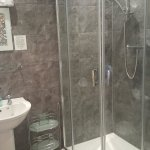 Modern and clean tiled en-suite shower room.