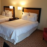 large enough room with sitting chair next to the two beds