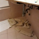 Tiled sink skirting fell off. Smashing all over the floor and on my foot. No one came to clean i
