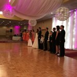 Bridal party standing in front of sweetheart table.