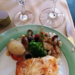 Grilled cod fish and baked potatoes and vegetables