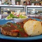 Pork chop with Cajun dirty rice, salad and Italian bread.