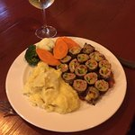 Beef tenderloin stuffed with bell peppers and cheese on a tomato & onion sauce with mash & veg