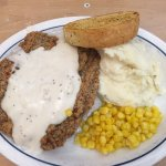 Country fried steak, bread, mashed potatoes, and a small serving of corn.
