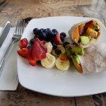 A breakfast wrap with fruit, sweet potato, avocado