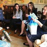 The mother-to-be opens gifts in the B&B's cozy antique living room.