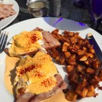 Eggs benedict with ham and potatoes