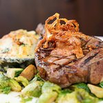 18oz. Bone-in KC Strip, Tobacco Onions, Manchego Cheese Scalloped Potatoes, Sautéed Brussels Spr