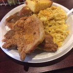 Fried Pork chop with mac and cheese, mashed potatoes and cornbread