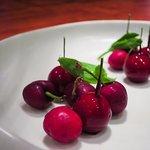 Fake cherries alongside real cherries.