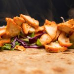 Grilled chicken tikka on a bed of fresh salad on handmade, wholewheat paratha bread.