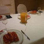 Desayuno continental básico: bollo, zumo de naranja, y un poco de jamón y queso