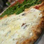 Pizza de quesos blanca, rúcula y tomate cherry, jamón y chorizo picante