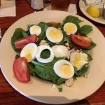 Spinach salad with boiled eggs, tomatoes, pecans, feta cheese