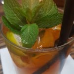 mixology drink with dark rum and mint leaves.
