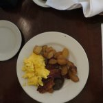 Scrambled eggs, bacon, sausge, fried potatoes and apples.