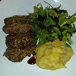 Pistachio crusted lamb rump with honey parsnip mash and rocket with caramelized onion.