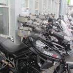 Fleet of rental motor cycles in front of hotel