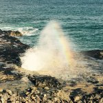 Lovely rainbow spray at Spouting Horn feature in the lava rocks