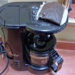 Notice used coffee bag on top of coffee maker