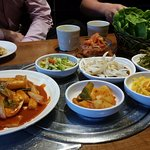 Topokki and complementary sides: kimchi, potatoes, spring onions, onion in soy sauce, pickled ra