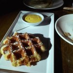 Free-range egg and a waffle with compote, passion fruit, and maple