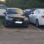 Car parked with driver's side at end of bay