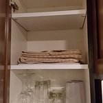 Kitchen cabinet with glasses, kitchen towels.