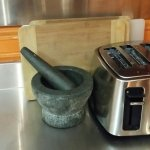 Cutting boards, toaster, pestle and mortar.