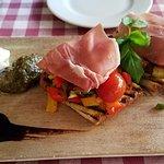 Bruschetta with prosciutto, pesto, goat cheese, and balsamic vinegar
