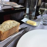 Une tache sur la nappe à l'arrivée cachée par la coupelle de beurre par le Maître d'hôtel