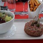 Tartare de boeuf accompagné de frites et d'une salade verte.