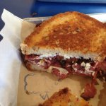 Gluten free bread with pastrami, caramelized onions and goat cheese