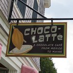 Cafe sign above outdoor seating.