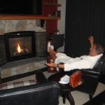 A happy husband in fluffy robe in front of fireplace to end the night!