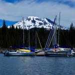 a photo from the pontoon, taking a picture of the middle sister in between boats.
