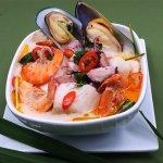 Deliciosa sopa picante de mariscos tailandesa con mejillones, pescado, pulpo, calamares y camaro