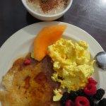 Homemade oatmeal, scrambled cheese eggs, fresh fruit and pancakes.