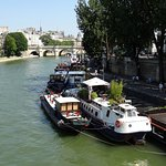 Multiple houseboats moored up along the River Seine, leading towards the oldest bridge in Paris