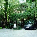 La cour ombragée, la terrasse couverte de vigne vierge, et la facade de l'auberge