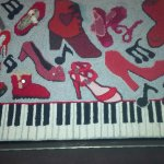 Hooked rug which hangs above the piano