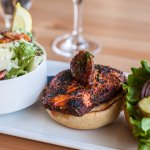Cajun Salmon Burger topped with a tomato jam and a side of our heart healthy caesar salad